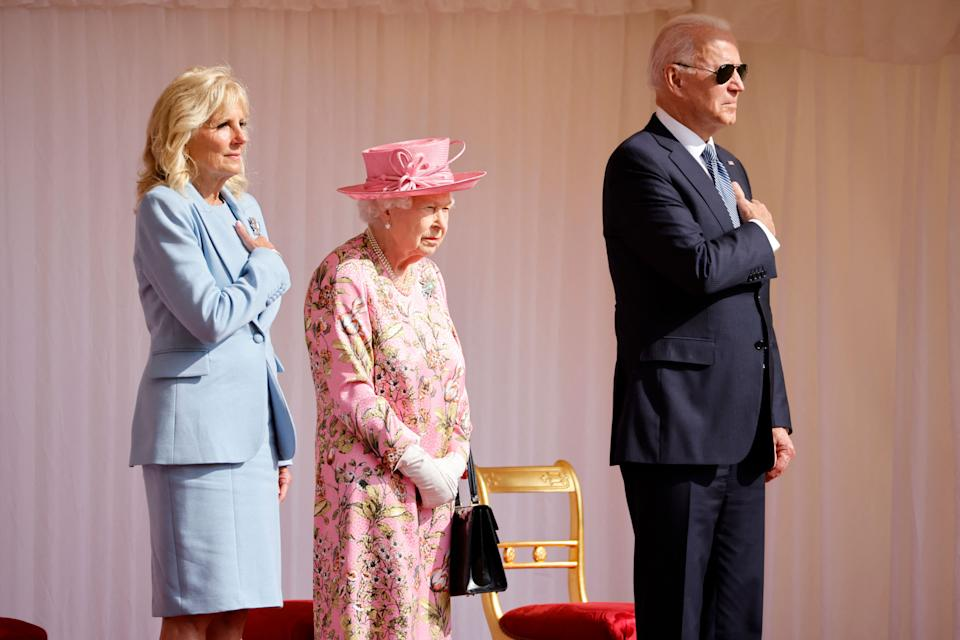 US President Joe Biden (R) and US First Lady Jill Biden (L) stand beside Britain's Queen Elizabeth II as a Guard of Honour formed of The Queen's Company First Battalion Grenadier Guards give a Royal Salute during the US National Athem at Windsor Castle in Windsor, west of London, on June 13, 2021. - US president Biden will visit Windsor Castle late Sunday, where he and First Lady Jill Biden will take tea with the queen. (Photo by Tolga Akmen / AFP) (Photo by TOLGA AKMEN/AFP via Getty Images)