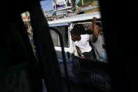 An employee waits for customers to board a bus in Port-au-Prince, Haiti, Saturday, July 10, 2021, three days after President Jovenel Moise was assassinated in his home. (AP Photo/Matias Delacroix)