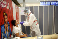 A health worker collects a nasal swab sample for COVID-19 test, at the Roissy Charles de Gaulle airport, outside Paris, Saturday, Aug. 1, 2020. Travelers entering France from 16 countries where the coronavirus is circulating widely are having to undergo virus tests upon arrival at French airports and ports.(AP Photo/Thibault Camus)