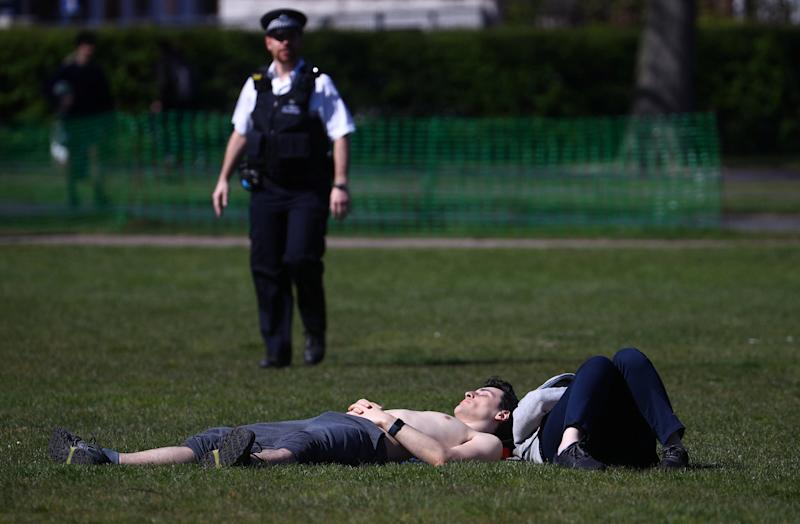 A police officer approaches Londoners enjoying in the spring heatwave: REUTERS