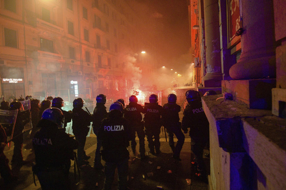 Carabinieri police wearing helmets, foreground, clash with protesters throwing flares, late Friday, Oct. 23, 2020, in Naples, southern Italy. Protesters in Naples, angry over a just-imposed 11 p.m. to 5 a.m. regional curfew and by the local governor's vow to put the region under lockdown to try to tame surging COVID-19 infections, clashed with police on Friday night. (Alessandro Pone/LaPresse via AP)