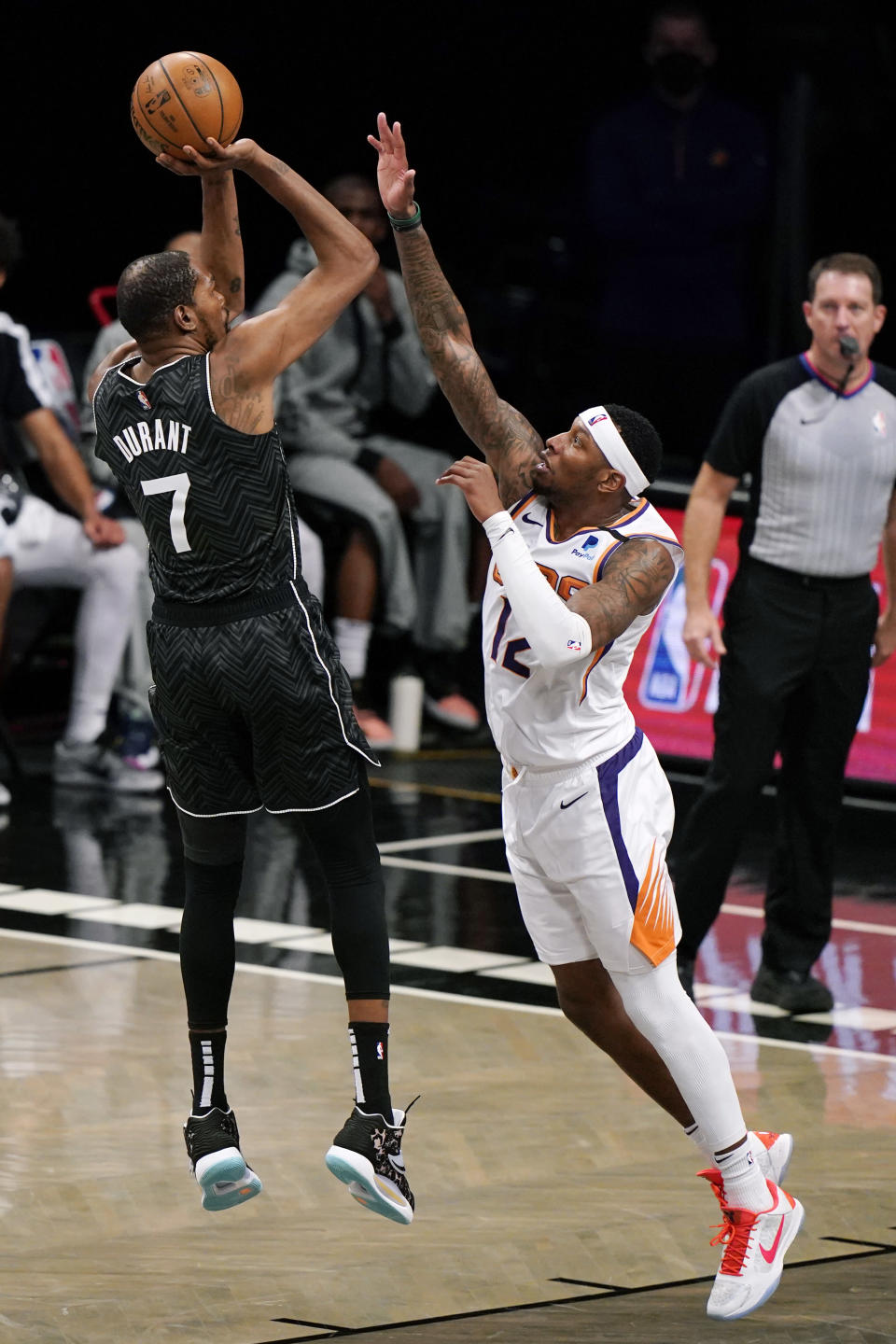 Phoenix Suns forward Torrey Craig (12) defends Brooklyn Nets forward Kevin Durant (7) as Durant shoots during the second quarter of an NBA basketball game, Sunday, April 25, 2021, in New York. (AP Photo/Kathy Willens)