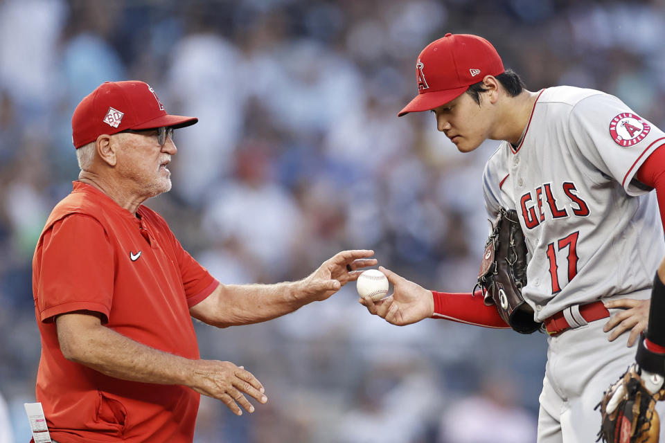 Los Angeles Angels manager Joe Maddon takes the ball from pitcher Shohei Ohtani during the first inning of the team's baseball game against the New York Yankees on Wednesday, June 30, 2021, in New York. (AP Photo/Adam Hunger)