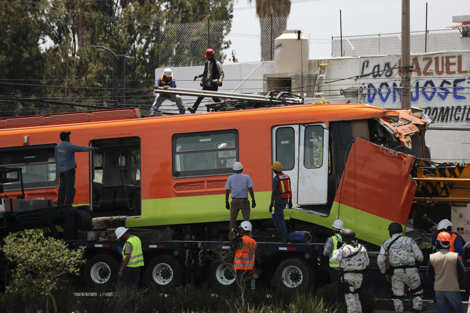 Workers remove a damaged subway car after it was lowered, with the help of a crane, to the ground from a collapsed elevated section of the metro, in Mexico City, Tuesday, May 4, 2021. The elevated section of the metro collapsed late Monday, killing at least 23 people and injuring at least 79, city officials said. (AP Photo/Marco Ugarte)