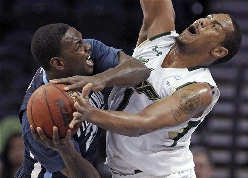 Villanova forward JayVaughn Pinkston, left, runs into South Florida forward Ron Anderson Jr. as he drives to the basket during the first half of an NCAA college basketball game Wednesday, Feb. 15, 2012, in Tampa, Fla. (AP Photo/Chris O'Meara)
