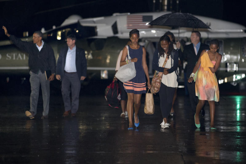 Malia Obama, center, walks with an unidentified girl and sister Sasha Obama, right, toward Air Force One as their father President Barack Obama, far left, waves at a waiting crowd before boarding Air Force One at Cape Cod Coast Guard Air Station, Mass., on Sunday August 18, 2013, at the conclusion of their family vacation on the island of Martha's Vineyard. (AP Photo/Jacquelyn Martin)