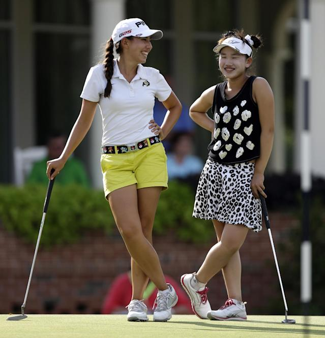 Lucy Li, right, laughs with playing partner Jessica Wallace, left, before finishing their round during the second round of the U.S. Women's Open golf tournament in Pinehurst, N.C., Friday, June 20, 2014. (AP Photo/Bob Leverone)