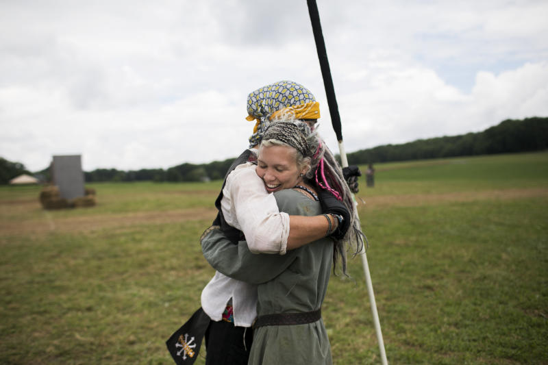 Attendees hug on the field while training for battle.  (Maddie McGarvey for HuffPost)
