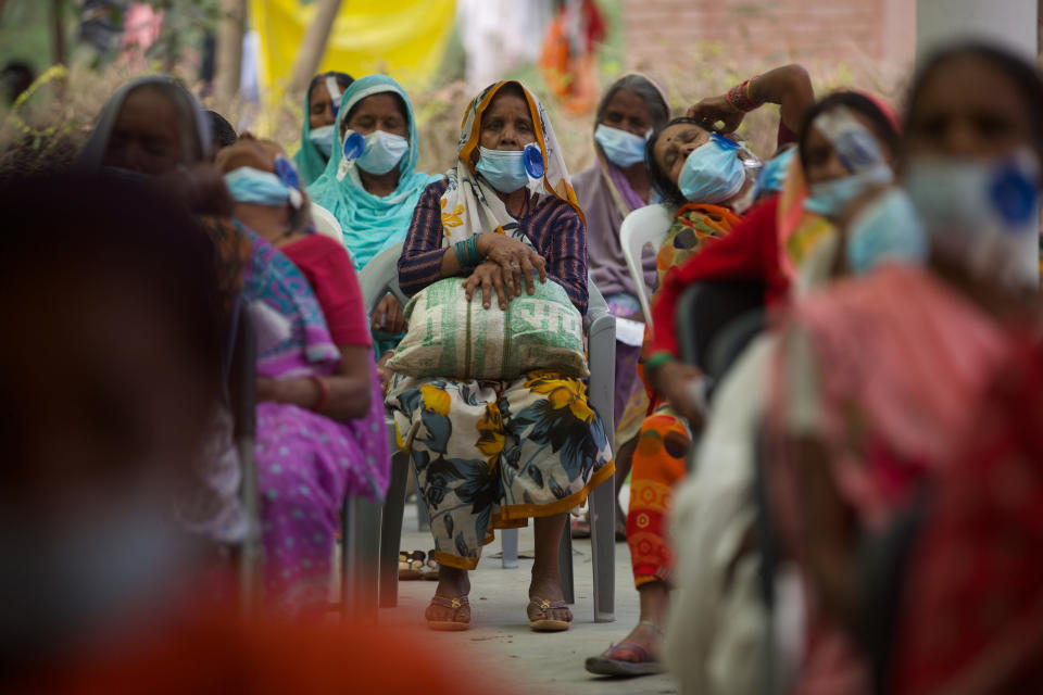 """Nepalese patients wait for their follow up after cataract surgery with Dr. Sanduk Ruit at an eye camp in Lumbini, 288 kilometers (180 miles) south west of Kathmandu, Nepal, March 31, 2021. Nepal's """"God of Sight"""" eye doctor renowned for his innovative and inexpensive cataract surgery for the poor is taking his work beyond the Himalayan mountains to other parts of the world so there is no more unnecessary blindness in the world. Ruit, who has won many awards for his work and performed some 130,000 cataract surgery in the past three decades, is aiming to expand his work beyond the borders of his home country and the region to go globally. (AP Photo/Bikram Rai)"""
