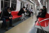 People wearing face masks travel in the subway, as the country is hit by an outbreak of the new coronavirus, in Beijing