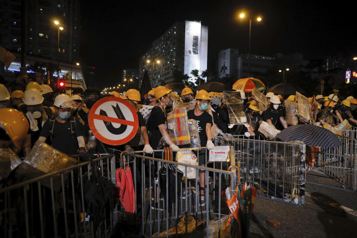 Protesters with protection gear hold home-made shield as they prepare to face off with policemen in Sha Tin District in Hong Kong, Sunday, July 14, 2019. Police in Hong Kong have fought with protesters as they broke up a demonstration by thousands of people demanding the resignation of the Chinese territory's chief executive and an investigation into complains of police violence. (AP Photo/Kin Cheung)
