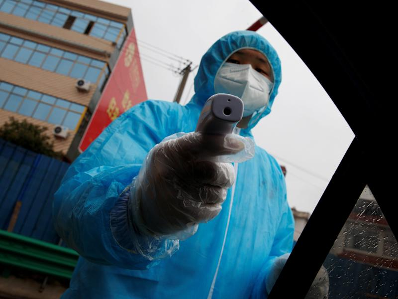 A medical worker holds a thermometer to check a passenger's temperature at a checkpoint as the country is hit by an outbreak of the novel coronavirus in Susong County, Anhui province, China, February 6, 2020. REUTERS/Thomas Peter