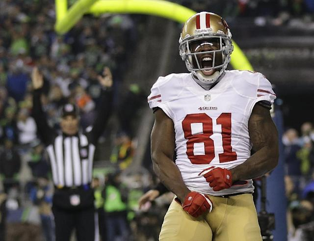 """FILE - In this Jan. 19, 2014 file photo, San Francisco 49ers' Anquan Boldin celebrates his touchdown catch during the second half of the NFL football NFC Championship game against the Seattle Seahawks, in Seattle. Boldin says he will be back with the San Francisco 49ers next season. Boldin wrote on his Twitter page Monday, March 3, 2014, that he's """"returning to San Francisco. A spokesman for the 49ers said the team had no immediate comment. (AP Photo/Marcio Jose Sanchez, File)"""