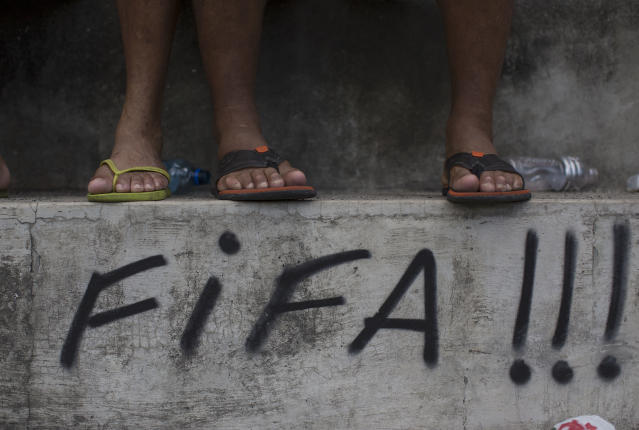 In this April 27, 2014 photo, residents watch an amateur soccer match in the Olaria neighborhood of Rio de Janeiro, Brazil. The high costs of hosting the upcoming World Cup, blamed in part by the late rush to get projects done, ignited a wave of public criticism from a population already tired of poor public services and widespread corruption. Many of the protests during last year's Confederations Cup were aimed at FIFA, and more are expected next month. (AP Photo/Leo Correa)