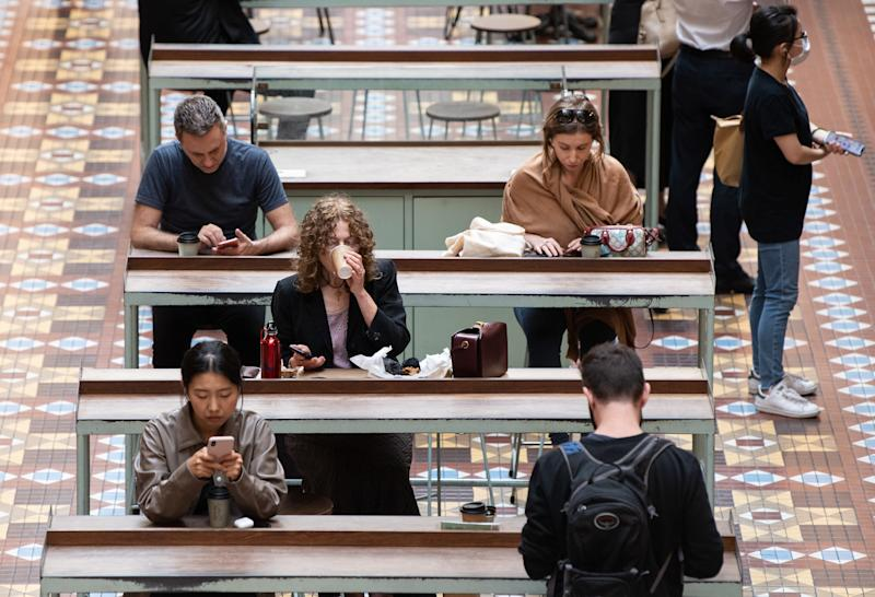 People are pictured sitting at a Sydney cafe ahead of an Australia-wide shutdown of cafes, restaurants and licensed venues.