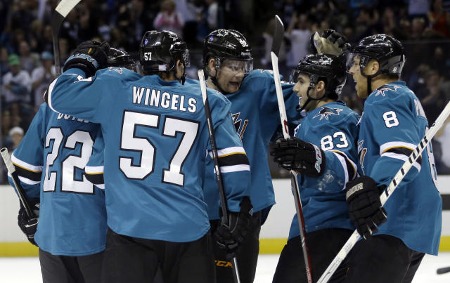 San Jose Sharks' Dan Boyle (22) celebrates his goal with teammates during the first period of an NHL hockey game against the New York Rangers on Tuesday, Oct. 8, 2013, in San Jose, Calif. (AP Photo/Marcio Jose Sanchez)