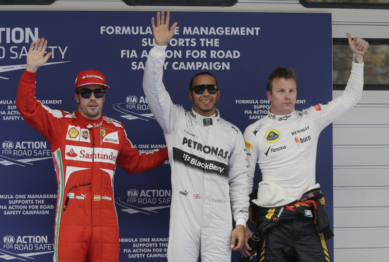 Mercedes driver Lewis Hamilton, centre, of Britain waves to the crowd after winning the qualifying session for the Chinese Formula One Grand Prix in Shanghai, China, Saturday, April 13, 2013. Lotus driver Kimi Raikkonen, right, of Finland finished second and Ferrari driver Fernando Alonso of Spain third. (AP Photo/Mark Baker)