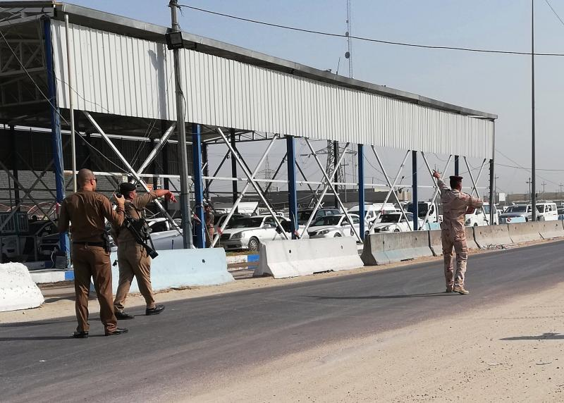 Security forces reopen a checkpoint after the explosion outside Karbala, Iraq, Saturday, Sept. 21, 2019. A bomb exploded on a minibus packed with passengers outside the Shiite holy city of Karbala Friday night, killing and wounding civilians, Iraqi security officials said. (AP Photo/Hadi Mizban)