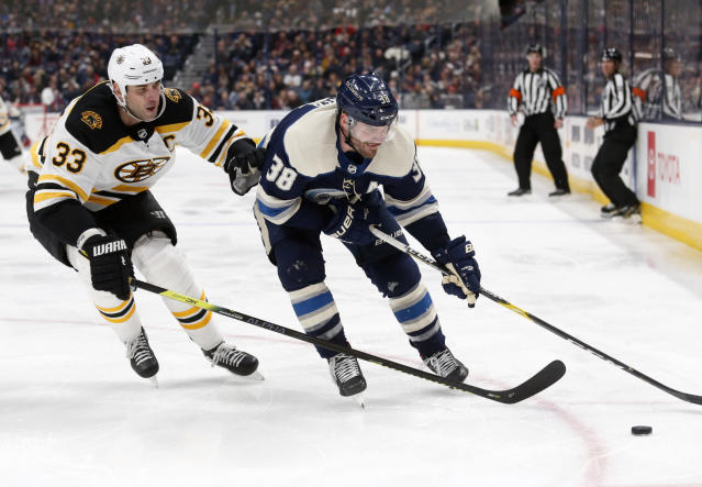 Columbus Blue Jackets forward Boone Jenner, right, chases the puck in front of Boston Bruins defenseman Zdeno Chara, of Slovakia, during the second period an NHL hockey game in Columbus, Ohio, Tuesday, Jan. 14, 2020. (AP Photo/Paul Vernon)