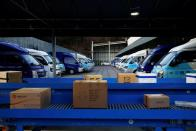 Parcels are conveyed as trucks for delivery are parked at a CJ Logistics distribution center in Gwangju