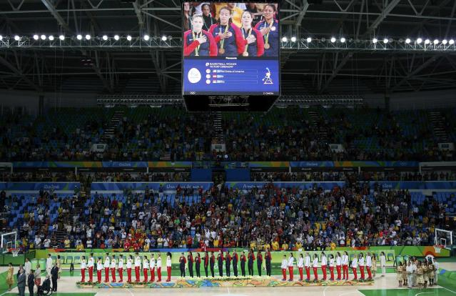 2016 Rio Olympics - Basketball - Final - Women's Gold Medal Game USA v Spain - Carioca Arena 1 - Rio de Janeiro, Brazil - 20/8/2016. United States players are seen on large screen as they stand for the playing of the U.S. National Anthem during the medal presentation ceremony for the women's basketball. REUTERS/Chris Helgren FOR EDITORIAL USE ONLY. NOT FOR SALE FOR MARKETING OR ADVERTISING CAMPAIGNS.