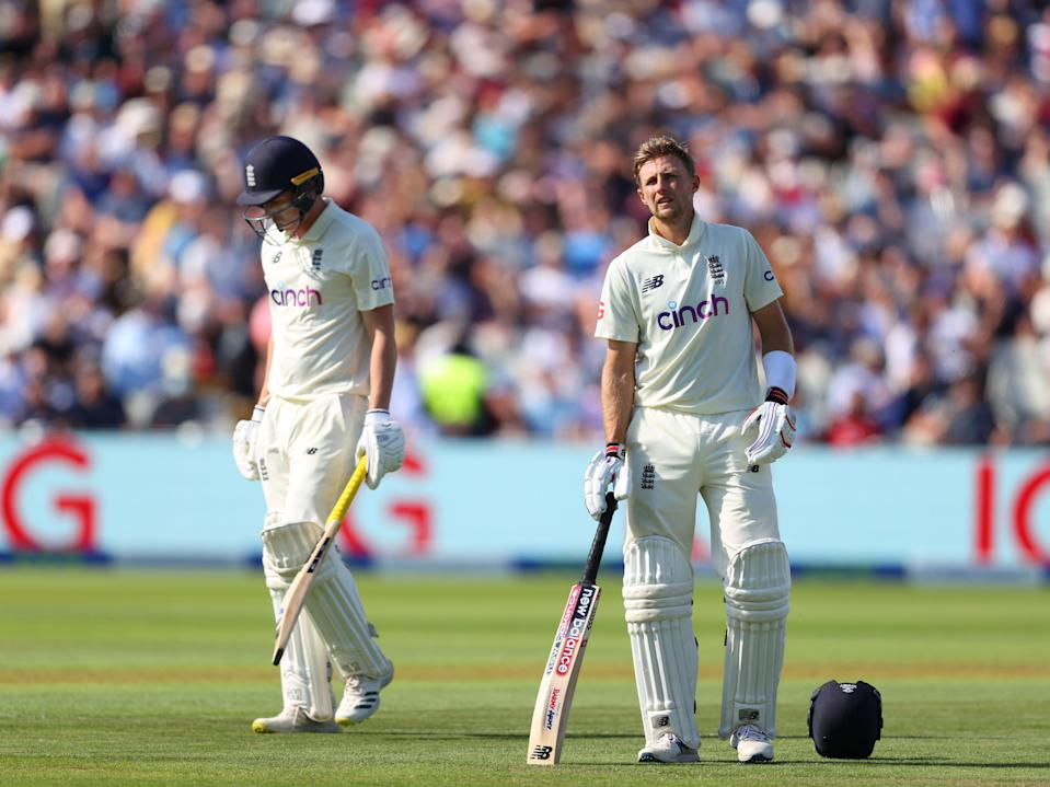 England batsman Dan Lawrence walks off after being dismissed for 0 as captain Joe Root looks on (Getty)