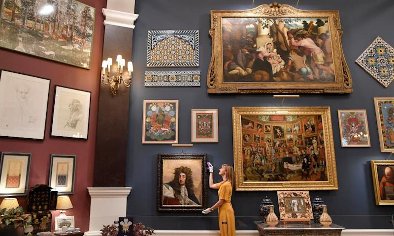 A curator adjusts a painting from the Prince and Patron exhibition at Buckingham Palace.