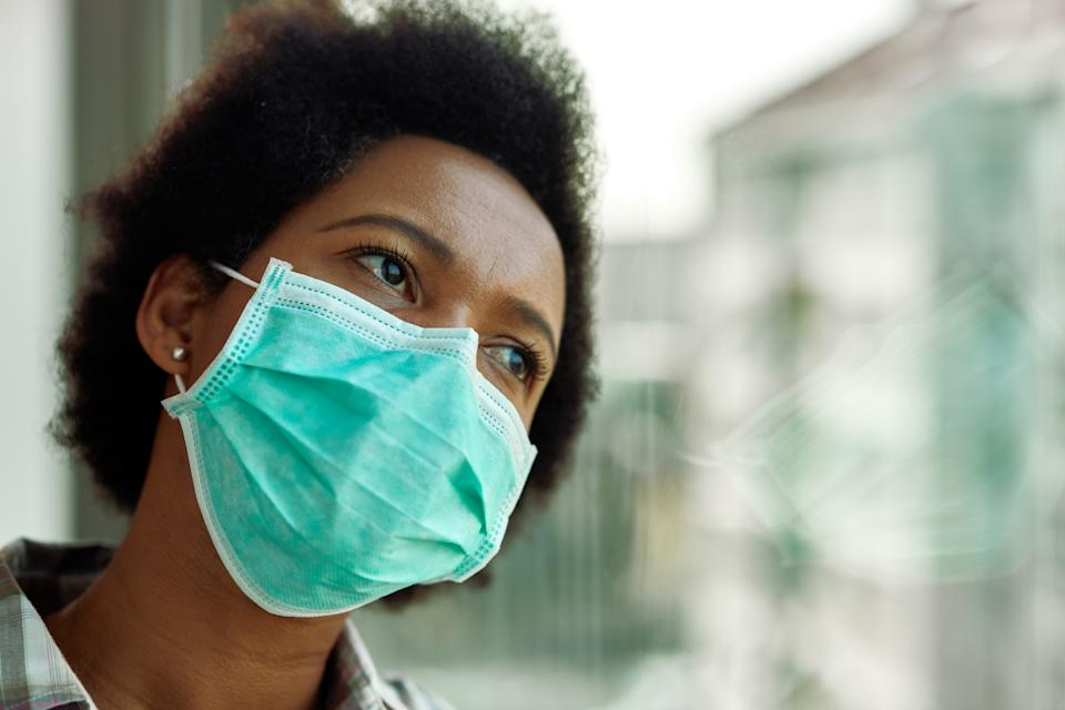 Distraught black woman with face mask thinking while looking through the window at home.