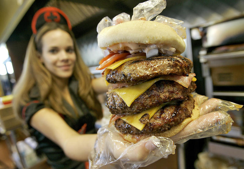 Courtney Chapman, a waitress dressed as a nurse at the Heart Attack Grill, holds up a triple bypass burger (PA)