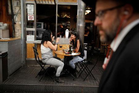 An ultra-Orthodox Jewish man walks past women at a bar in Jerusalem May 11, 2017. Picture taken May 11, 2017. REUTERS/Amir Cohen