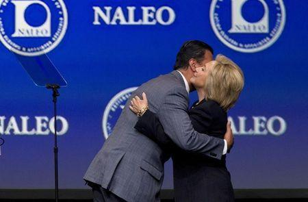 Former Secretary of State Hillary Clinton (R) is embraced by Alex Padilla, president of the National Association of Latino Elected and Appointed Officials (NALEO), as she arrives onstage to speak at the NALEO conference in Las Vegas, Nevada June 18, 2015. REUTERS/Steve Marcus