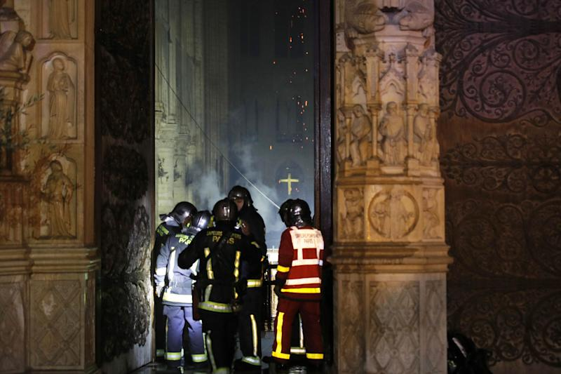 Paris Fire brigade members are seen at an entrance that looks into the Notre Dame Cathedral as a fire continues to burn in Paris, France, April 15, 2019. (Photo: Philippe Wojazer/Reuters)