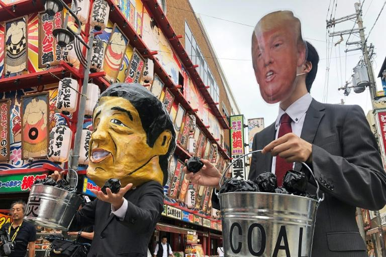 Protesters wearing masks of world leaders including Japan's Prime Minister Shinzo Abe and US President Donald Trump demonstrate against climate change at the G20 summit in Osaka