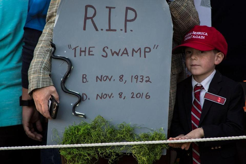 """A boy dressed up as the president next to headstone that reads """"R.I.P. 'the swamp.'"""" at the White House. (Photo: Getty Images)"""