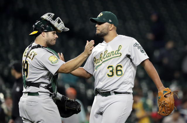 Oakland Athletics closing pitcher Yusmeiro Petit (36) and catcher Josh Phegley share congratulations after the team defeated the Seattle Mariners 9-3 in a baseball game Wednesday, Sept. 26, 2018, in Seattle. (AP Photo/Elaine Thompson)