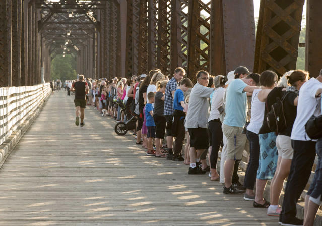 <p>Mourners join hands as thousands of people hold hands to remember last week's shooting victims by joining hands on the Bill Thorpe Walking Bridge in downtown Fredericton on Monday, Aug. 13, 2018. (Photo from The Canadian Press/Stephen MacGillivray) </p>