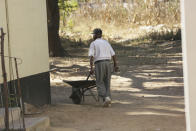 An elderly man pushes a wheelbarrow at the Society for the Destitute Aged care home in Harare's Highfield township, Zimbabwe, Saturday June, 26, 2021. The economic ravages of COVID-19 are forcing some families in Zimbabwe to abandon the age old tradition of taking care of the elderly. Zimbabwe's care homes have experienced a 60% increase in admissions since the outbreak of the pandemic in March last year. (AP Photo/Tsvangirayi Mukwazhi)
