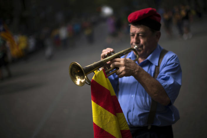 """Ferran Estrada Porta, 79, wearing the traditional cup or """"barretina"""" and holding a Catalan flag, plays his trumpet on the street in Barcelona, Spain, Tuesday, Sept. 11, 2012. Thousands of people demonstrated in Barcelona on Tuesday to join a rally demanding independence for Catalonia, in northeastern Spain, on the Catalan national day. (AP Photo/Emilio Morenatti)"""
