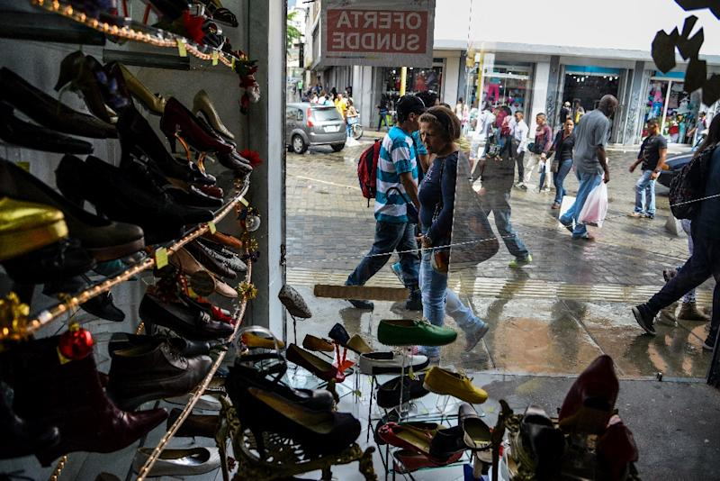 In the historic centre of Caracas, most storefronts carry signs sporting the government's seal and advertising 'Sundde sales' or a '30% Sundde discount' (AFP Photo/FEDERICO PARRA)