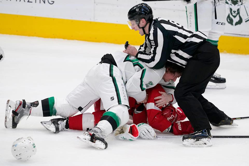 Linesman Libor Suchanek (60) attempts to break up a fight between Dallas Stars defenseman Sami Vatanen (45) and Detroit Red Wings center Vladislav Namestnikov, bottom, in the first period at American Airlines Center in Dallas on Tuesday, April 20, 2021.