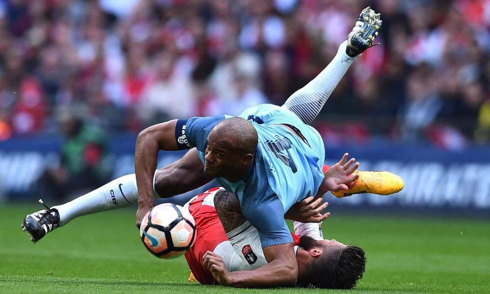Vincent Kompany vies with French forward Olivier Giroud during the FA Cup semi-final between Arsenal and Manchester City at Wembley