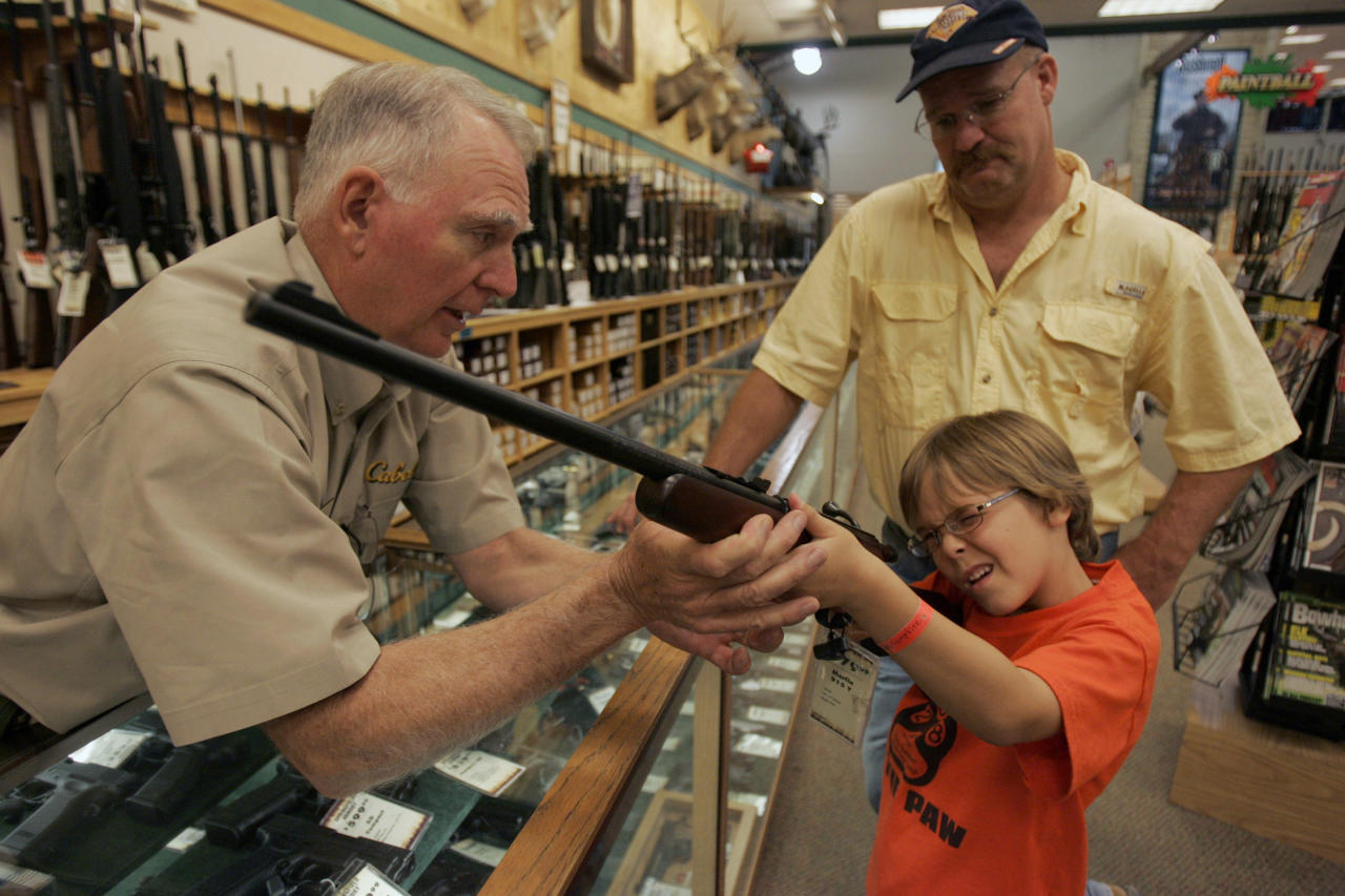 Hunter McConathy (C), 7, holds a hunting rifle with a short stock as his father Bryan (R) and Cabela's salesman Russ Duncan (L) watch him at the Cabela's store in Fort Worth, Texas June 26, 2008. Individual Americans have a right to own guns, the Supreme Court ruled on Thursday for the first time in history, striking down a strict gun control law in the U.S. capital.  REUTERS/Jessica Rinaldi (UNITED STATES)