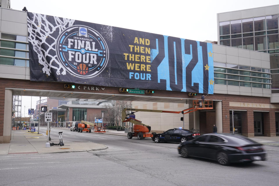 A worker ties down an NCAA college basketball tournament banner from a crosswalk, Wednesday, March 17, 2021, in Indianapolis. (AP Photo/Darron Cummings)