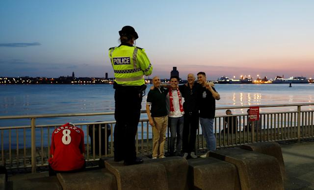 Soccer Football - Liverpool fans watch the Champions League Final - Liverpool, Britain - May 26, 2018 Liverpool fans and a police officer after losing the final as they stand beside the river Mersey near Albert Dock REUTERS/Peter Nicholls