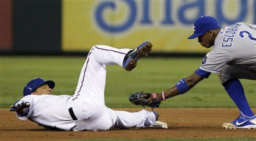 Texas Rangers' Alberto Gonzalez (14) beats the tag at second base for the double against Kansas City Royals shortstop Alcides Escobar (2) during the fourth inning of a baseball game, Tuesday, May 15, 2012, in Arlington, Texas. (AP Photo/LM Otero)