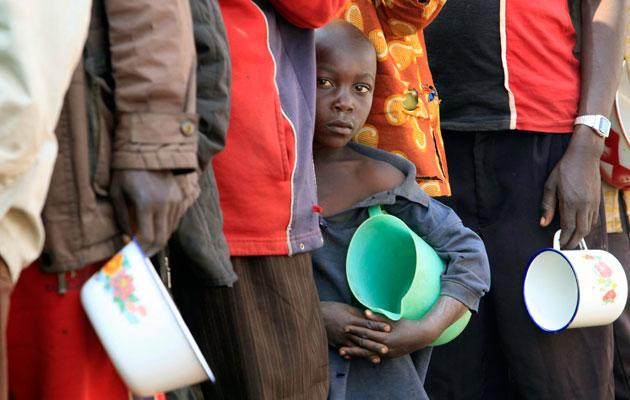 Congolese refugees queue for porridge at the Nyakabande refugee transit camp in Kisoro town, 521 km (324 miles) southwest of Uganda's capital Kampala July 8, 2012. Rebels in eastern Democratic Republic of Congo said on Sunday they seized the town of Rutshuru in North Kivu province after government forces abandoned it. REUTERS/James Akena