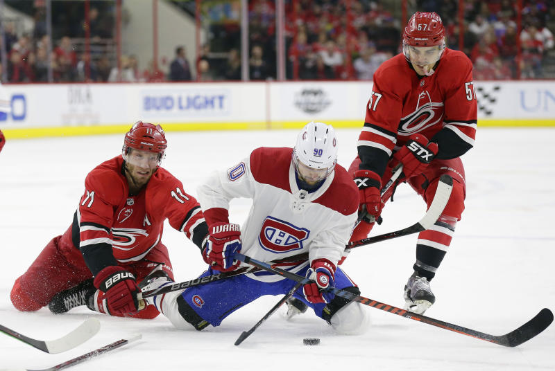 Carolina Hurricanes' Jordan Staal (11) and Trevor van Riemsdyk (57) skate for the puck with Montreal Canadiens' Tomas Tatar (90), of Slovakia, during the second period of an NHL hockey game in Raleigh, N.C., Sunday, March 24, 2019. (AP Photo/Gerry Broome)