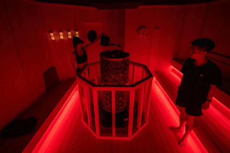 The exhibition contains seven saunas of various temperatures lit up atmospherically in bold colours from magenta to deep green