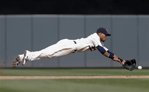 Minnesota Twins' Pedro Florimon dives successfully for a sharp grounder by Kansas City Royals' Miguel Tejada in the sixth inning in of a baseball game, Saturday, June 29, 2013 in Minneapolis. Florimon threw Tejada out at first. (AP Photo/Jim Mone)