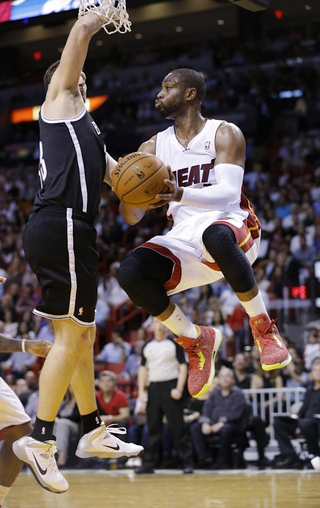 Miami Heat guard Dwyane Wade, center, looks for an open teammate as he is guarded by Brooklyn Nets forward Mirza Teletovic, of Bosnia, during the first half of an NBA basketball game, Wednesday, March 12, 2014, in Miami. (AP Photo/Wilfredo Lee)